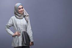 Lyckligt asiatiskt bära för muslimkvinna skyler den hållande bärbara datorn Arkivbilder