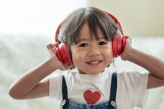 Lyckligt asiatiskt barn att tycka om lyssna till musik med hörlurar royaltyfri bild