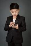 Lyckligt asiatiskt barn i den svarta dräkten som rymmer den digitala mobiltelefonen Royaltyfri Bild