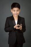 Lyckligt asiatiskt barn i den svarta dräkten som rymmer den digitala mobiltelefonen Royaltyfri Foto