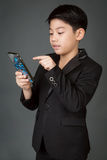 Lyckligt asiatiskt barn i den svarta dräkten som rymmer den digitala mobiltelefonen Royaltyfria Bilder