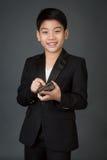 Lyckligt asiatiskt barn i den svarta dräkten som rymmer den digitala mobiltelefonen Arkivbilder