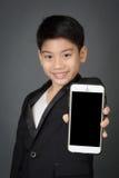 Lyckligt asiatiskt barn i den svarta dräkten som rymmer den digitala mobiltelefonen Fotografering för Bildbyråer
