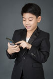 Lyckligt asiatiskt barn i den svarta dräkten som rymmer den digitala mobiltelefonen Arkivbild