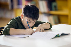 Lyckligt asiatiskt barn som gör läxa med leendeframsidan royaltyfria bilder