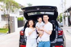 Lyckligt asiatiskt familjanseende på baksidan av SUV bilen med det leendet arkivfoton