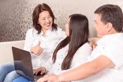Lyckligt asiatiskt familjsammanträde på bärbara datorn royaltyfri fotografi