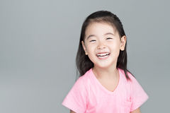 Lyckligt asiatiskt flickaleende på hennes framsida Royaltyfri Fotografi