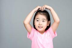 Lyckligt asiatiskt flickaleende på hennes framsida Arkivfoto