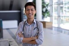 Lyckligt asiatiskt manligt doktorsanseende med armar som korsas i sjukhus arkivfoto