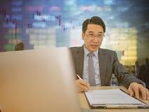 Lyckligt asiatiskt sammanträde för affärsman på hans skrivbord med aktiemarknadnolla arkivfoto