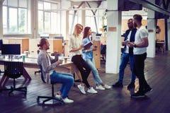 Lyckligt att arbeta tillsammans Grupp av ungt affärsfolk som meddelar, medan arbeta i kontoret royaltyfri foto