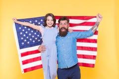 Lyckligt att vara amerikaner lycklig sj?lvst?ndighet f?r dag Skäggigt lyckligt le för man och för liten flicka med amerikanska fl arkivbilder