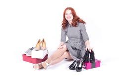 Lyckligt attraktivt kvinnasammanträde på golvet och måtten skorna Royaltyfria Foton