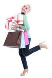 Lyckligt av att stå den unga kvinnan med shoppingpåsen och gåvaaskar Arkivbild
