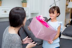 lyckligt av moder- och dotterasiat med gåvan med det rosa bandet Royaltyfri Bild