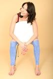 Lyckligt avkopplat gladlynt attraktivt sammanträde för ung kvinna på en vit stol Royaltyfri Bild