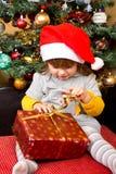 Lyckligt barn i ask för gåva för jul för jultomtenhattöppning Royaltyfria Bilder