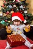 Lyckligt barn i ask för gåva för jul för jultomtenhattöppning Arkivfoton
