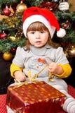 Lyckligt barn i ask för gåva för jul för jultomtenhattöppning Royaltyfri Fotografi