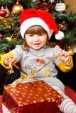 Lyckligt barn i ask för gåva för jul för jultomtenhattöppning Arkivfoto