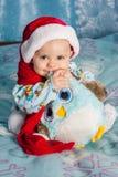 Lyckligt barn i den röda hatten för jul som rymmer en leksak Royaltyfri Fotografi