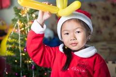 Lyckligt barn i den santa hatten med en gåva nära julgranen, Ch Royaltyfria Bilder