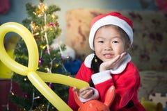 Lyckligt barn i den santa hatten med en gåva nära julgranen, Ch Royaltyfria Foton