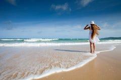 Lyckligt barn i den vita klänningen på havsstrand arkivbilder