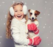 Lyckligt barn i vinterkläder med hunden Fotografering för Bildbyråer