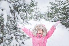 Lyckligt barn i vinterpark behandla som ett barn flickan i ett rosa omslag kastar utomhus- snö arkivbild