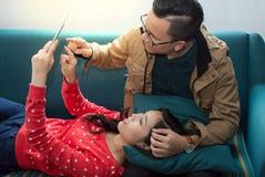 Lyckligt barn kopplade av asiatiska par som arbetar på den digitala minnestavlan Fotografering för Bildbyråer