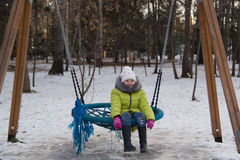 Lyckligt barn: lilla flickan på vippan för barn` s på vinterstaden parkerar royaltyfri foto