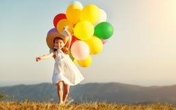 Lyckligt barn med ballonger på solnedgången i sommar arkivfoto