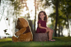 Lyckligt barn med en nallebjörn i parkera Royaltyfri Fotografi