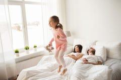 Lyckligt barn med leksaken och föräldrar i säng hemma arkivbild