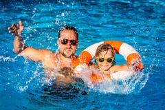 Lyckligt barn och fader som spelar i simbassäng Arkivfoto