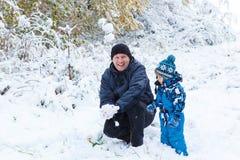Lyckligt barn och farsa som har gyckel med insnöad vinter arkivbild