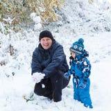 Lyckligt barn och farsa som har gyckel med insnöad vinter Arkivfoton