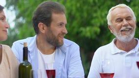 Lyckligt barn och pensionärpar som dricker vin och pratar, helg med föräldrar stock video