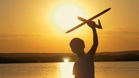 Lyckligt barn på en bakgrund av en orange himmel och sjö i sommar på solnedgången som spelar med ett leksakflygplan