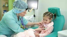 Lyckligt barn på mottagandet för doktors` s, sjuk unge för läkarundersökning, lyssnande barnlungastetoskop, behandling stock video
