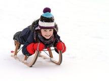 Lyckligt barn på pulkan i vinter Arkivfoto