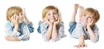 Lyckligt barn, pojke för liten unge som ner ligger på magen, hand på hakan, royaltyfri fotografi