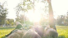Lyckligt barn som älskar pardanandeselfie med den smarta telefonen, medan ligga på gräset lager videofilmer