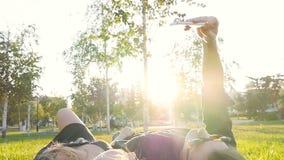 Lyckligt barn som älskar pardanandeselfie med den smarta telefonen, medan ligga på gräset arkivfilmer