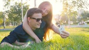 Lyckligt barn som älskar pardanandeselfie med den smarta telefonen, medan ligga på gräset stock video