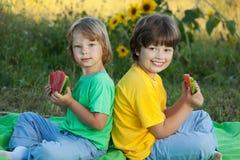 Lyckligt barn som äter vattenmelon i trädgård arkivbild