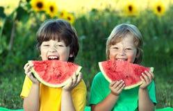 Lyckligt barn som äter vattenmelon i trädgård Två pojkar med frukt parkerar in royaltyfria foton