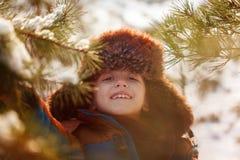 Lyckligt barn som går i en vinterskog i solig dag arkivbilder